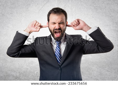 business man covering her ears over textured background  - stock photo