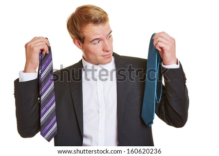 Business man deciding for tie and looking uncertain
