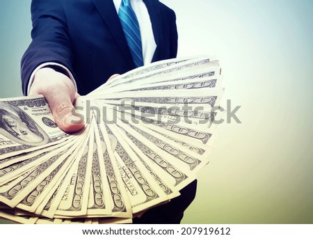 Business Man Displaying a Spread of Cash in Vintage Light - stock photo