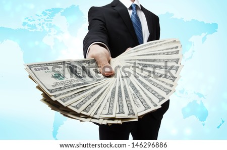 Business Man Displaying Spread of Cash over World Map - stock photo