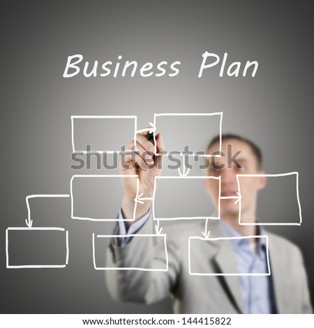 Business man drawing a business plan on a glass wall.