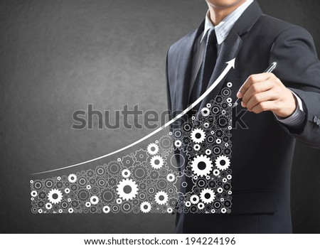 Business man drawing growing economy and industry represented by gears as a symbol of industrial activity - stock photo