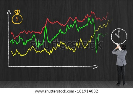 Business man drawing investor stock index graph on black wall - stock photo