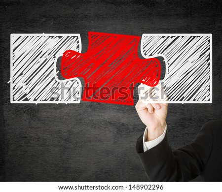 Business man drawing missing jigsaw puzzle piece on transparent drawing board - solution or teamwork concept - stock photo