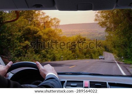 business man driving car in opposite directions to each other on the country road. - stock photo