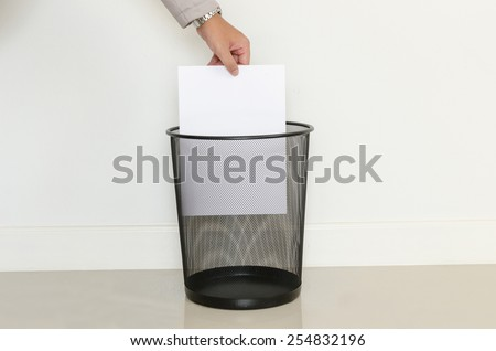 Business man drop paper in to recycle bin - stock photo