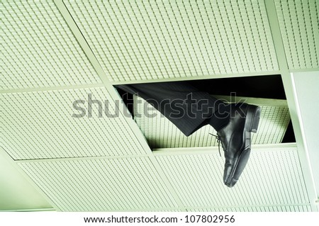 Business man escaping a meeting by climbing through the ceiling