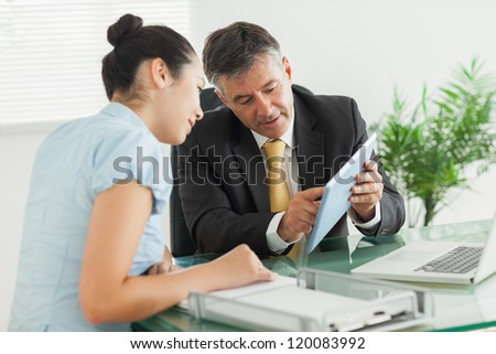 Business man explaining something to a woman with a digital tablet in an office - stock photo