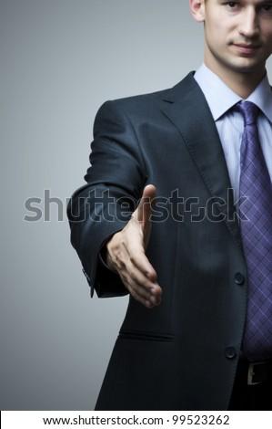Business man extending hand to shake - focus om hand - stock photo