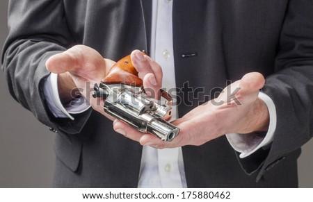 business man giving up a gun at work - stock photo