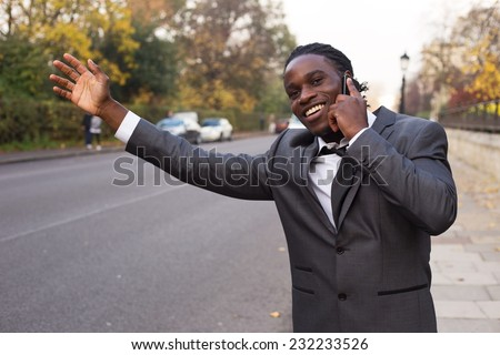 business man hailing a taxi on the phone. - stock photo