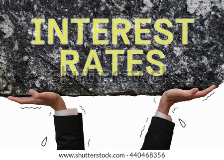Business man hand carrying and making effort to push up big stone with message INTEREST RATES. Business concept on get trouble situation in paying interest rates burden.  - stock photo