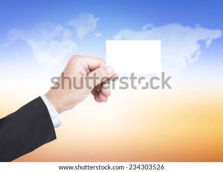 Business man hand holding a blank business card over blurred world map shaped clouds in the sunset. - stock photo