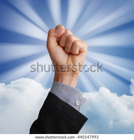 Business man hand holding fist and raising in the air in business concept in glory, happy, victory, winning, confident, or success. Blue sky, white cloud background with sun ray effect.  - stock photo