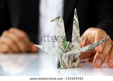 business man hand holding origami paper cranes, money concept - stock photo