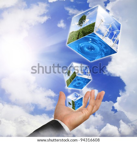 Business man hand holding with nature water drop and wind  turbines farm on sky - stock photo