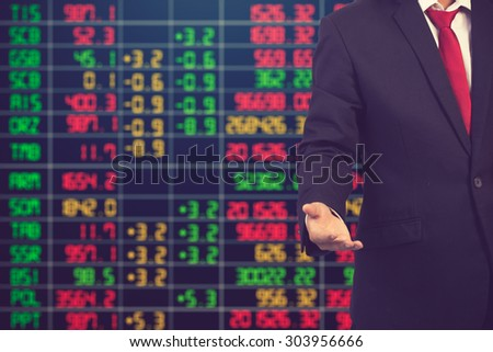 Business Man hand holding with stock market background vintage color