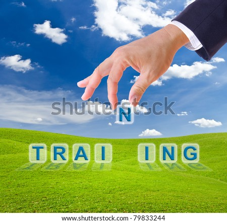 business man hand made training word buttons on green grass meadow - stock photo