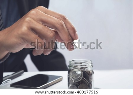Business man hand putting coin into a glass with copy space vintage tone.