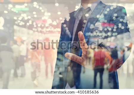 business man hand touching virtual screen on blurred people background - stock photo