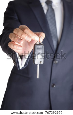 business man Hand with a car key. Isolated on white background.