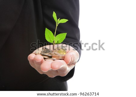 business man hand with a green plant growing from pile of money coins, concept for finance - stock photo