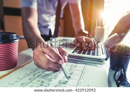 business man hand working and laptop with on on architectural project at construction site at office desk in office  - stock photo