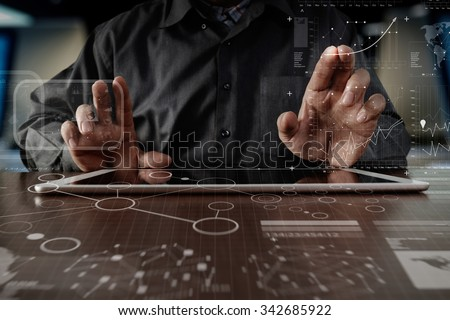 business man hand working on digital tablet computer with digital layer business strategy and social media diagram on wooden desk - stock photo