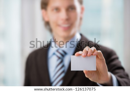Business man handing a blank business card at his office
