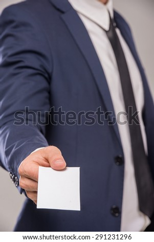Business man handing a blank business card over gray background.