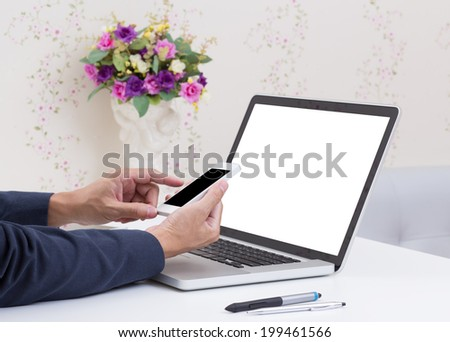 Business man hands using mobile phone with blank screen laptop computer background - stock photo