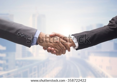 business man handshake isolated on blurred brightening city urban metropolis background,agreement of financial and business hands concept.improvement/development of world class business conception. - stock photo