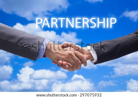business man handshake over blurred blue sky backgrounds with word Partnership, business hands concept. - stock photo