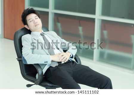 Business man having a quick sleep leaning back in his chair
