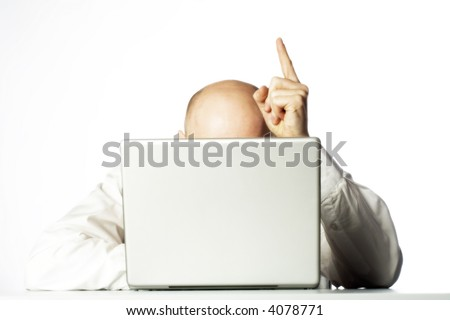 Business man hidden behind laptop computer with finger raised above bald head in an aha moment.
