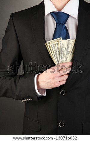 Business man hiding money in pocket on black background