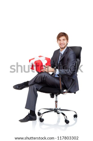 Business man hold gift box in chair, businessman give red present, sitting in armchair, happy smile, Isolated over white background - stock photo