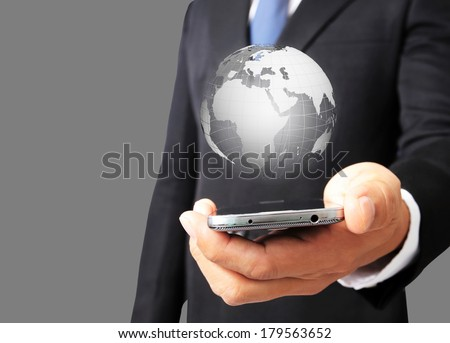 Business man hold smart phone with glowing digital wire globe  - stock photo