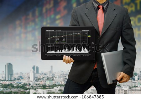 Business man hold the digital tablet and graph report
