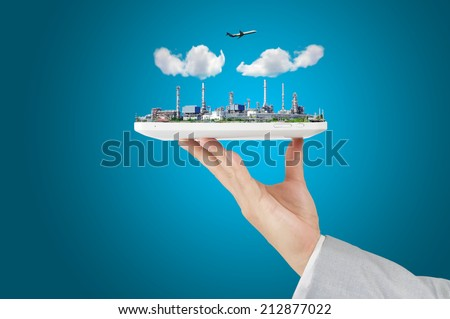 Business man hold touch pad or tablet with Oil refinery Plant or Factory, airplane and cloud - stock photo