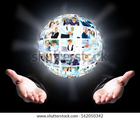 Business man holding a ball of people on a dark background - stock photo
