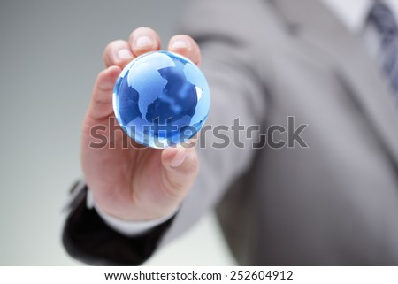 Business man holding a blue globe in his hand symbol for global business, communications or environmental conservation - stock photo