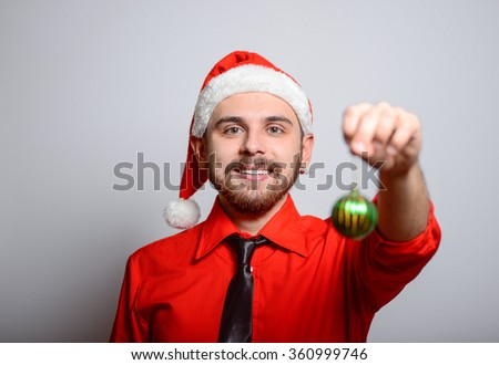Business man holding a Christmas toy. Winter, corporate party, Christmas hat isolated portrait of a man on a gray background, studio photo. - stock photo