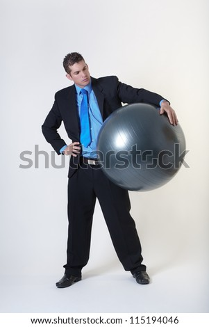 business man holding a gym ball - stock photo