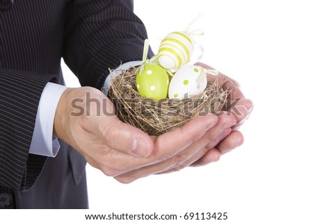 Business man holding a nest with many colorful easter eggs - stock photo
