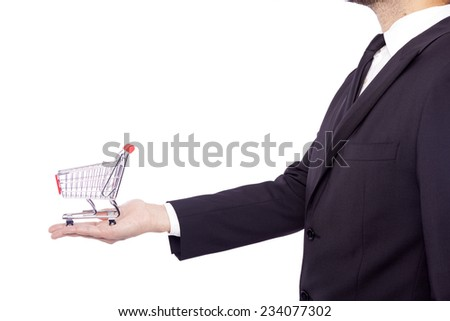 Business man holding a shopping cart, isolated over white background