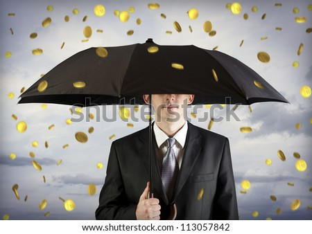 Business man holding an umbrella, money falling from the sky - stock photo