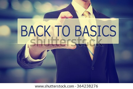 Business man holding Back To Basics on blurred abstract background