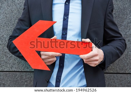 Business man holding big red arrow to the left - stock photo