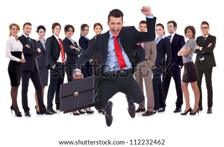 business man holding briefcase jumping with his business team formed of young businessmen and businesswomen standing over a white background - stock photo
